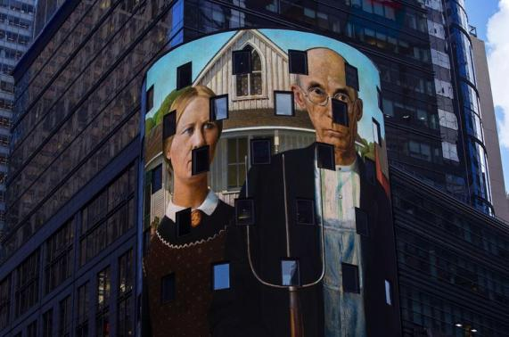 """A reproduction of the art work """"American Gothic"""" is displayed on a digital billboard in Times Square, New York"""